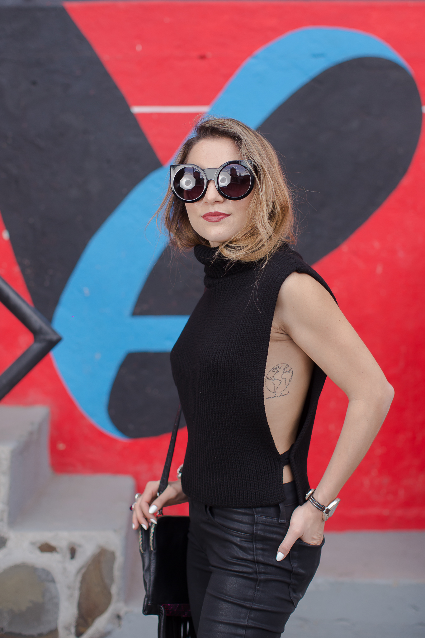 Whitney's Wonderland UK Top Fashion Blogger wears Wildfox Couture sunglasses, Joe's Jeans knit open sides knit vest, coated ripped jeans, and Kurt Geiger bow heels